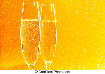 Two glasses of champagne on golden sparkling background.