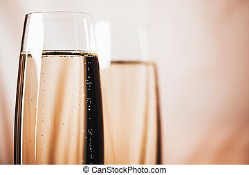 Two glasses of champagne on light background.