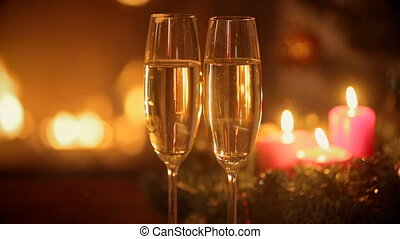 Two glasses of champagne on table in front of burning fireplace at Christmas eve.