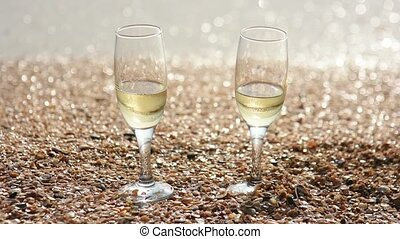 Two glasses of champagne stand on the sand with small shells by the sea, in the background waves wash the shore