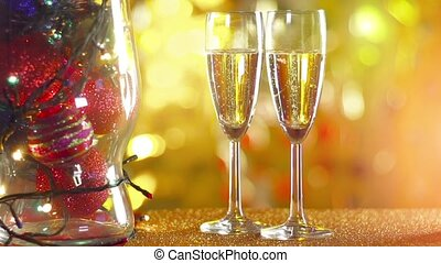 Two glasses of champagne with bokeh lights in the background.