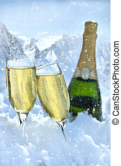 Two glasses of champagne with bottle in snow