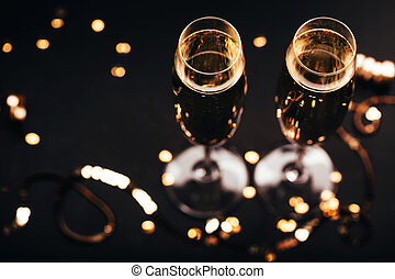 Two glasses of champagne with decoration on black elegant background.