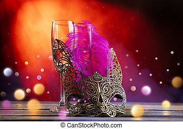 Two glasses of champagne with mask on the table