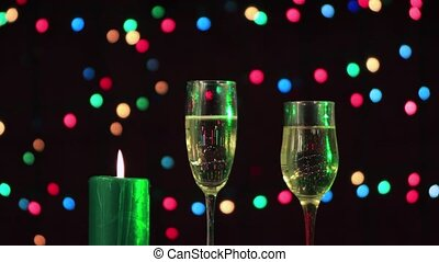 Two glasses of Christmas champagne, a green candle is burning next to it.