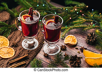 Two glasses of Christmas mulled wine with spices and orange slices