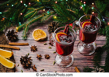 Two glasses of Christmas mulled wine with spices and orange slices on a wooden rustic table