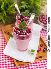 Two glasses of cranberry dessert with fresh cranberries on the tray