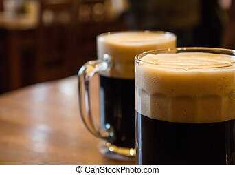 Two glasses of dark beer on table