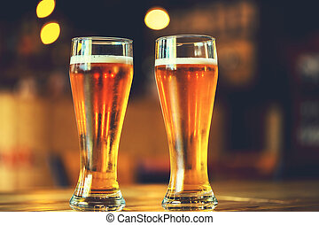 Two glasses of fresh cold light beer on a wooden bar counter...