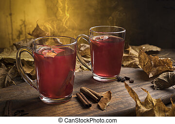 Two glasses of hot red mulled wine with spices, orange slices, cinnamon stick and anise star with.