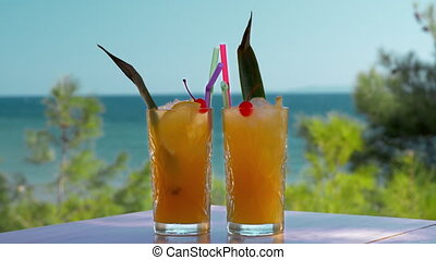 Two glasses of iced fruit drinks on sea background. Vacation time