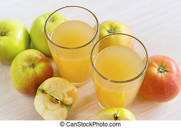 two glasses of juice, Apple juice, whole apples and apples cut in half