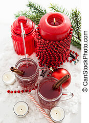 Two glasses of mulled wine and candle with Christmas decorations around