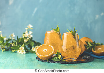 Two glasses of orange ice drink with fresh mint on wooden ...