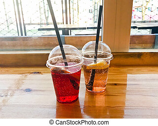 Two glasses of plastic red and yellow refreshing cold tasty sweet raspberry strawberry cherry orange peach lemon fruit lemonade natural with a straw and syrup bubbles