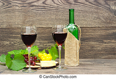two glasses of red wine and fruits on wooden background