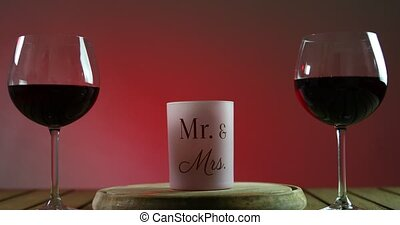 Two glasses of red wine standing on a table with candle on the wooden platform. Camera is moving backwards.
