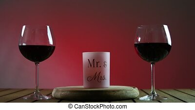 Two glasses of red wine standing on a table with candle on the wooden platform.