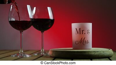 Two glasses of red wine standing on a table with candle on the wooden platform. Waiter pouring wine into the wineglass.