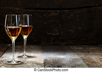 Two glasses of sherry on brown wooden background with copyspace