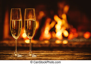 Two glasses of sparkling champagne in front of warm ...