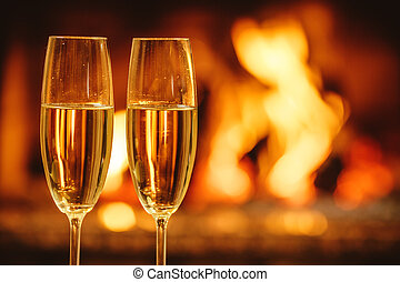 Two glasses of sparkling champagne in front of warm fireplace. C