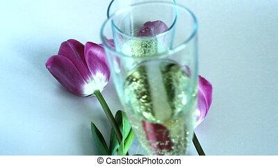 Two glasses of sparkling wine and red tulips, bubbles...