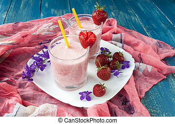 Two glasses of strawberry smoothie with straws on a wooden table