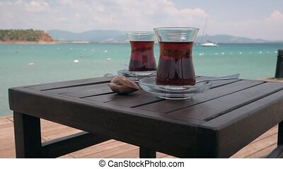 Two glasses of turkish tea on the table with anchored sailing yacht in the sea on the background. 4k, Establishing Shot.