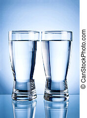 Two glasses of water on a blue background