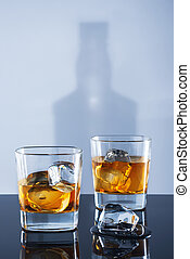 Two glasses of whisky and ice on a light background with a...