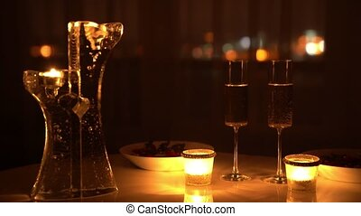 Two glasses of wine and candles in the dark with city lights at the background