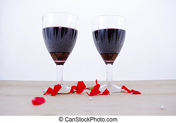 Two glasses of wine on a table with flower petals