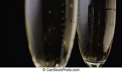 Two glasses with champagne closeup of bubbles rise up. Black...