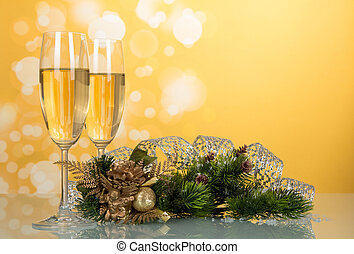 Two glasses with champagne, pine branch decorated with ribbon, New Year's souvenir on yellow background