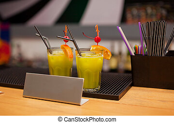 Two glasses with exotic cocktails on the bar counter
