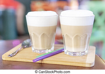 two glasses with latte on the table