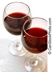 two glasses with red wine standing on table-cloth