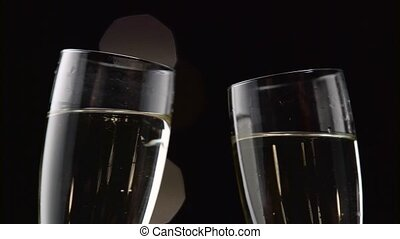 Two glasses with sparkling champagne toasting over holiday. Bokeh blinking black background. Close up