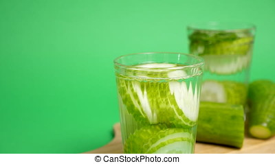 Two glasses with water infused with cucumber on a green...