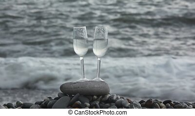 two glasses with wine standing on stone on beach against sea surf, woman walking