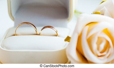 Two gold rings and white roses on the table of the wedding ceremony