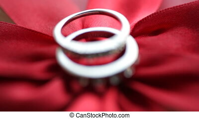 Two gold rings on a red bow