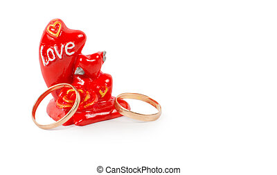Two gold rings with a token of love in the form or a red...