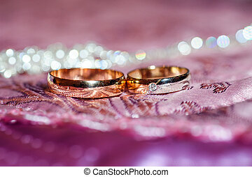 Two gold wedding rings lie on a pillow close up
