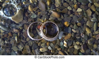 Two gold wedding rings lying on beach stones shining on sun light close up macro. Transfusion of light on rings. ocean wave washed on them
