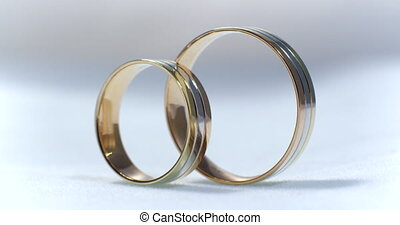 Two gold wedding rings lying on white-gray surface shining...