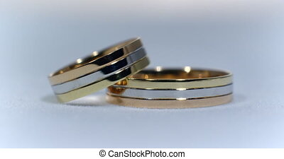 Two gold wedding rings lying on white-gray surface shining with light close up macro. Transfusion of light on rings.