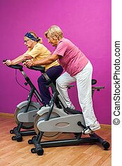 Two golden agers doing spinning in gym.